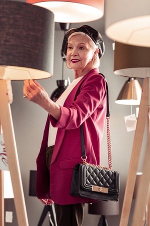 Madam in lighting store. Stylish bright aging madam wearing leather hat pink jacket thoroughly selecting a new floor-lamp in lighting store