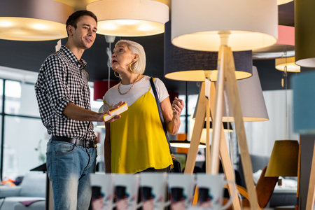 Elderly woman with boyfriend. Beautiful stylish aging dame wearing bright top lively discussing lamps purchasing with a young nice-appealing tall boyfriend with brown hair.