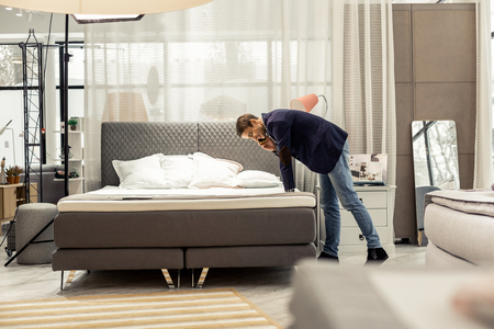 Consulting according purchasing. Attractive mature stately brown-haired man in navy blazer and blue denim pants consulting via phone about new bed purchasing in store.