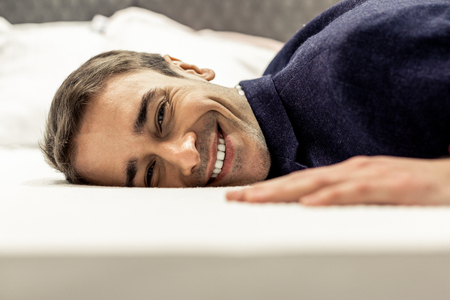 Male face portrait. Portrait of smiling handsome face of male with brown eyes light stubble lying on white bed sheets
