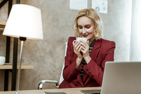 Short-haired businesswoman. Peaceful and calm good-looking blonde woman carrying hot cup of tea with both hands