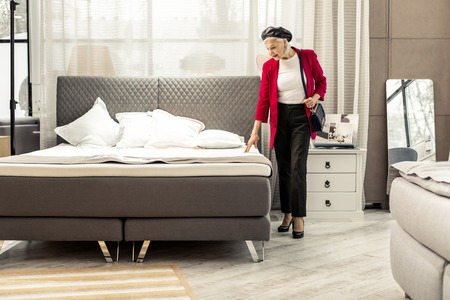 Selecting new bed. Bewitching fashionable silver-haired aging woman wearing black trendy leather beret, fuchsia jacket, black pants and bag joyfully selecting new grey bed in store