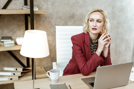 Connected hands. Short-haired woman with blue eyes wearing matching lipstick and jacket and being thoughtful at work