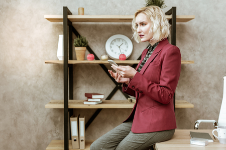 Typing messages. Serious good-looking lady in red outdated jacket leaning on table surface and being confused with received message