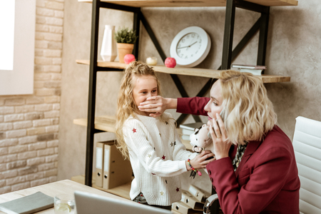 Daughter yelling nearby. Irritated blonde businesswoman shutting mouth of her daughter while she behaving loudly Imagens