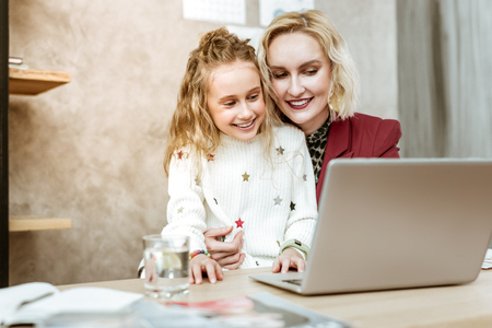 Girl being interested. Good-looking adult mother with wide smile carrying her curious daughter in front of laptop