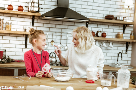 Weight of flour. Cheerful blonde good-looking lady pointing on dirty nose of her laughing little kid