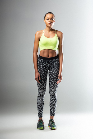 Healthy body. Pleased dark-skinned female standing isolated on grey and looking straight at camera