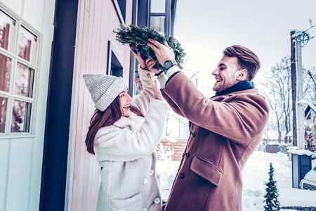 Having fun outside. Cute loving couple having fun outside while bringing home Christmas decorations