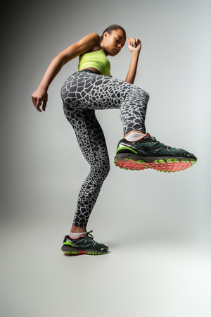 Sport uniform. Serious brunette raising right leg while doing stretching task