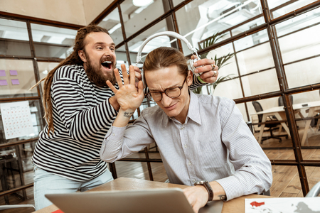 Try it. Positive bearded man holding white headphones while distracting his colleague from work