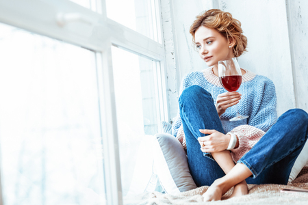 All alone. Beautiful young woman looking into the window while holding a glass of wine