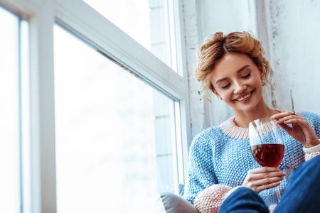 Boisson préférée. Femme positive gaie souriant tout en regardant le vin