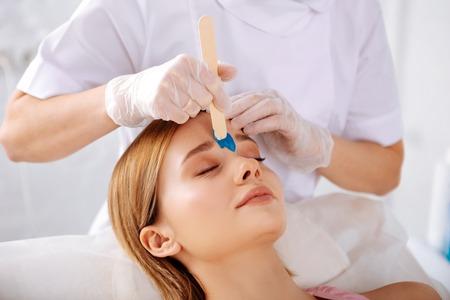 Augenbrauenkorrektur. Schöne blonde Frau, die einen Enthaarungssalon zur Augenbrauenkorrektur besucht
