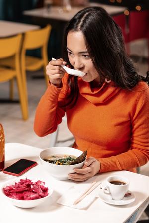La cuillère, c'est mieux. Pour la jolie fille brune, il est plus pratique d'avoir le dîner commandé avec une cuillère en céramique, pas des baguettes.