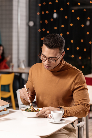 Exotic cuisine. Pleasant guy in polo-neck seeing the Japanese dish for the first time and looking at it suspiciously.