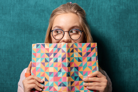 Not so funny. Portrait of pretty blond girl trying to hide her sincere smile behind a book cover.