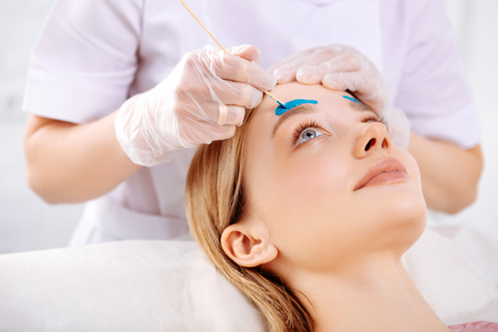 Waxing forehead. Specialist wearing gloves waxing forehead and correcting eyebrows of beautiful client Stock Photo