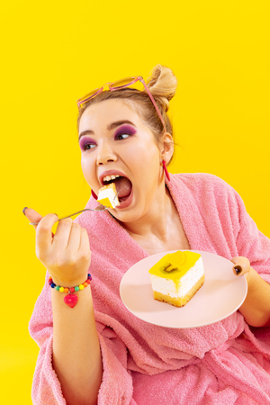 Opening mouth. Woman with pink eye shades opening her mouth wide while eating sweet cake 写真素材