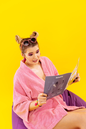 Reading magazine. Young blonde-haired woman wearing pink bathrobe reading modern magazine Stock Photo