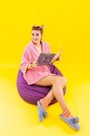 Home clothes. Young woman wearing home clothes sitting on beanbag chair reading fashion magazine