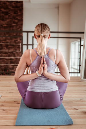 Online master classes. Light-haired young woman sitting in lotus posture on yoga mat and connecting hands behind her back