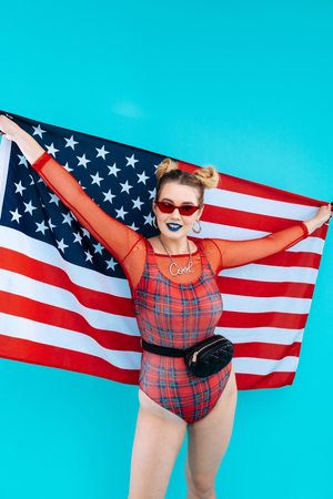 American flag. Cheerful woman wearing stylish red bodysuit feeling patriotic while holding American flag