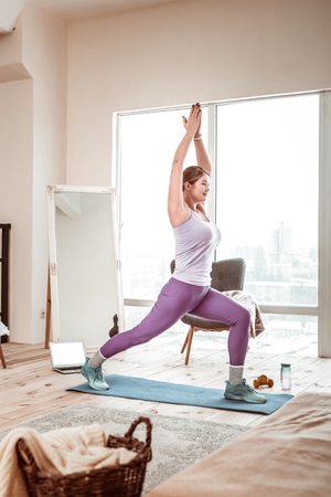 Rubber yoga mat. Resolute sportive woman having active exercise session while staying at home for all alone Stock Photo