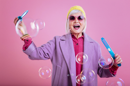 Feeling lovely. Stylish retired woman feeling lovely and cheerful while playing with bubbles