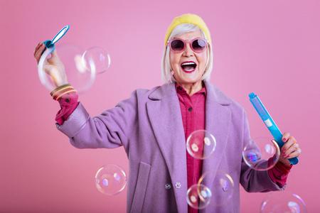 Sientiendome amado. Elegante mujer jubilada que se siente encantadora y alegre mientras juega con burbujas