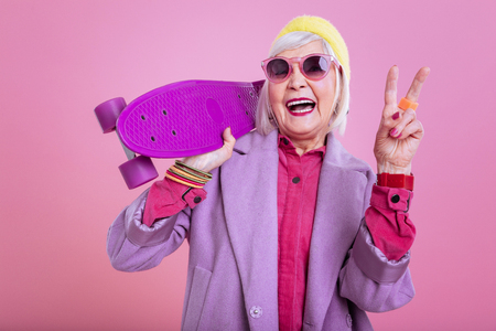 Showing piece sign. Laughing modern retired woman showing piece sign after riding skateboard
