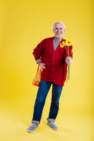 Kind-hearted man. Cheerful kind-hearted retired man giving holding sunflowers for lovely wife Reklamní fotografie