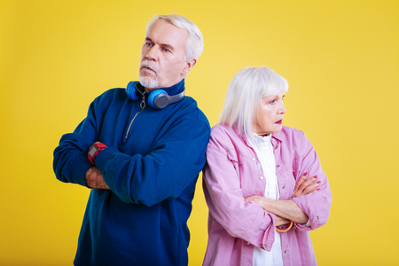 Feeling offended. Couple of stylish modern pensioners feeling offended after little quarrel