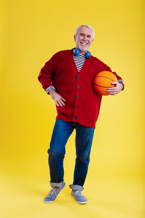 Love basketball. Modern pensioner wearing jeans and sneakers leading healthy lifestyle and loving basketball