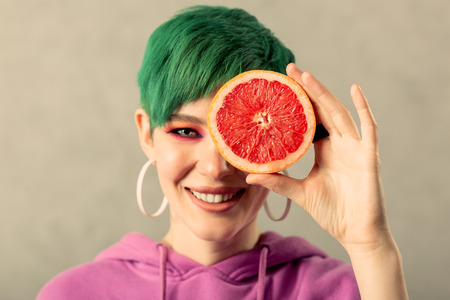 Delicious fruit. Portrait of a beautiful woman smiling while holding a grapefruit