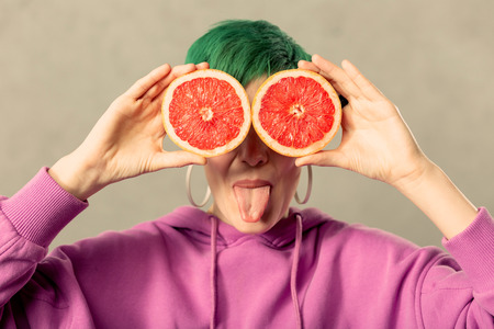 So playful. Nice happy young woman showing her tongue while standing with grapefruit halves Banque d'images - 118835046