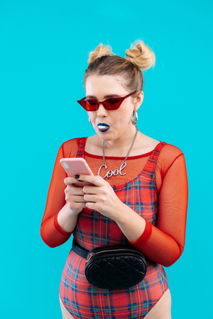 Typing message. Blonde woman wearing red bodysuit chewing bubble gum and typing message