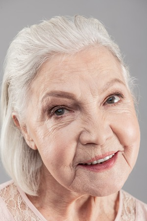 Working as model. Beaming white-haired senior woman with grey eyes having makeup on and hairstyle done