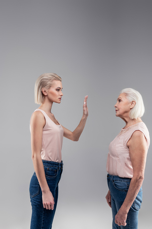 Woman showing palm. Categorical blonde short-haired beautiful girl shutting her mother up with resolute gesture Zdjęcie Seryjne