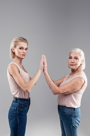 Serious old mother. Peremptory young lady and old grey-haired woman raising hands and connecting them