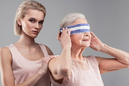 Serious unpleasant girl. Plotting blonde beautiful girl blocking vision of old helpless woman while staying behind Stockfoto