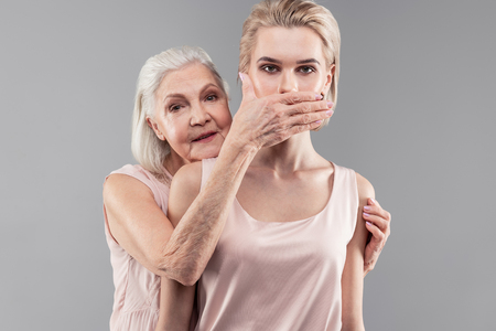Wrinkled hands. Strict old-fashioned grey-haired mother covering mouth of her daughter while guarding her