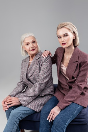 Spending time together. Good-looking young lady sitting next to her short-haired mother while they both wearing jackets