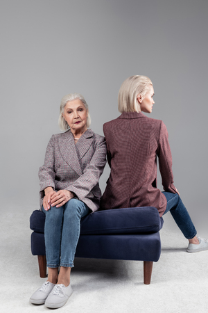 Senior lady. Resolute blonde young girl in red jacket back while her short-haired mother sitting facing forward Stock Photo