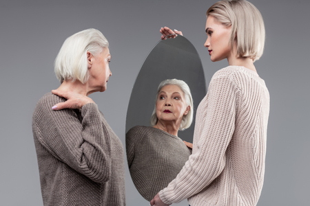 Daughter carefully carrying. Short-haired old lady posing while checking herself up in mirror with help of trustful daughter