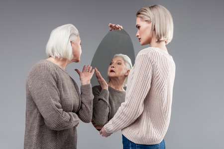 Trustful daughter. Pretty old woman wearing knitted grey sweater and inspecting appearance in mirror reflection