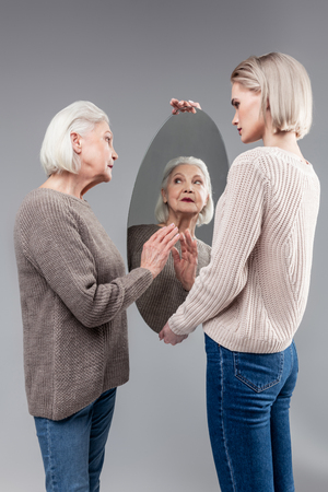 Touching clean surface. Curious old lady touching surface of oval mirror in hands of her daughter while getting ready Zdjęcie Seryjne