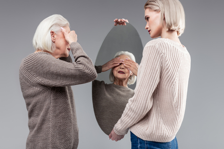 Wearing sweater. Grey-haired senior lady covering her eyes with both hands before looking on herself in mirror