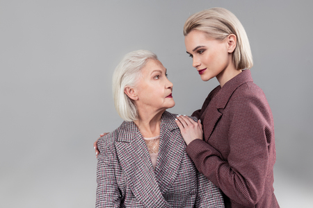 Touching shoulders. Smiling appealing girl with dark lipstick looking directly into eyes of her old mother Imagens