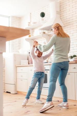 Feeling amazing. Happy funny good-looking mother and daughter feeling amazing dancing together 版權商用圖片